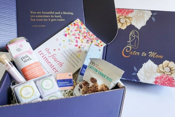 An image showing the contents of a past Cater to Mom subscription box in a royal blue box. Products  such  as personal care items, gourmet food, breastfeeding products,  and a book are included in the box.