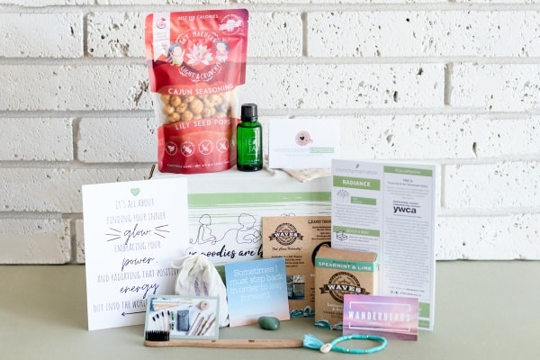 An  image of the contents of a past  Crunchy Mama new mom subscription box against a white brick background. The image  shows snacks, personal  care items, jewelry,  and affirmations.