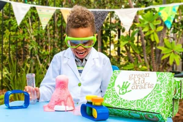 A preschool aged boy stands at a table while conducting a science experiment included in Green kid Crafts preschool subscription box