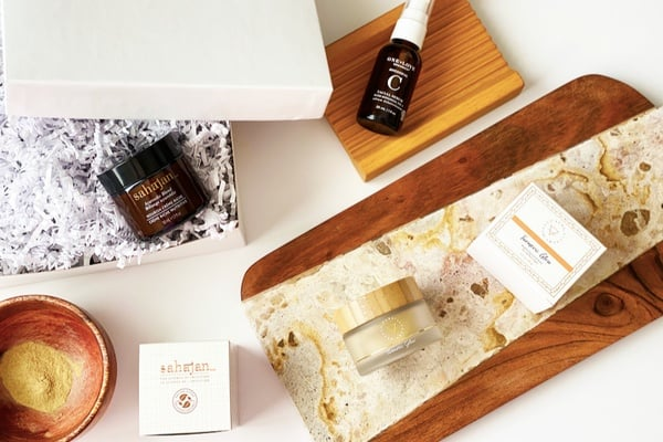 A birds eye photograph of the Laurel and Reed subscription box, which  shows  various natural beauty and personal care items displayed  against a neutral wood and marble background.