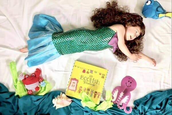 A image of a preschool girl in a mermaid costume lying on a bed with fish and ocean themed stuffies and a Bookish Wardrobe box