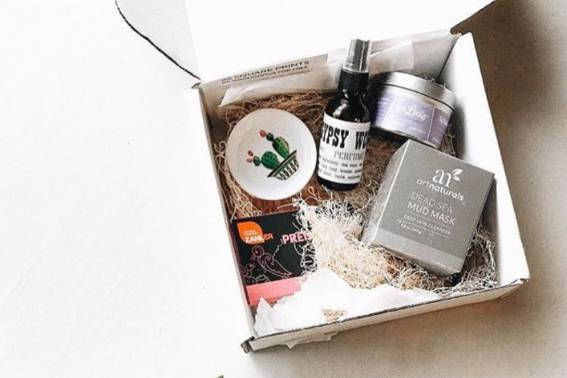 A birds eye photograph of the Mama Bird subscription box which shows products in  a past box. Products include housewares, personal care items, and beauty items.