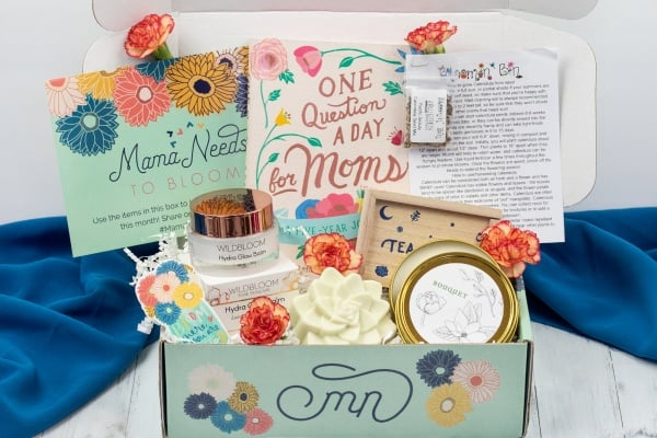 An image showing the content of a past Mama Needs Box. Products include  beauty items, a  journal, a  candle and other self care items and treats for  a new mother
