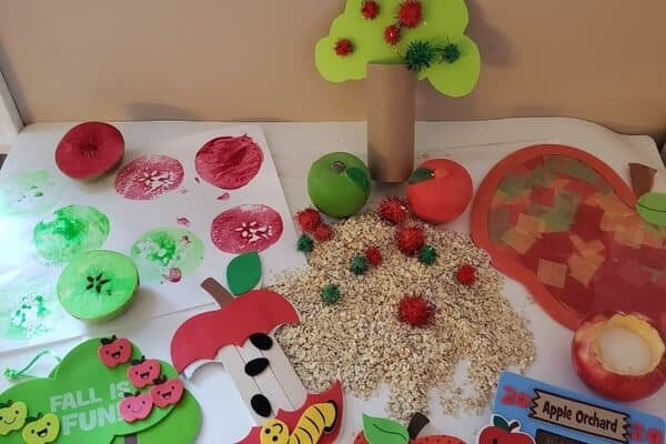A photo showing activities from the My Busy Box Buddy preschool in a box subscription kit. The activities are apple themed and show crafts, nature activities, counting activities, books, and sorting activities