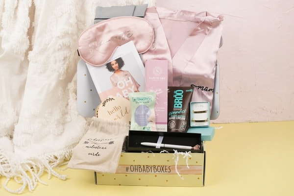 An image of the contents of a past Oh Baby Box. The contents  include  baby milestone cards, hand cream, a pen, an eye mask, and more.