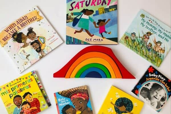 A photograph showing 7 different childrens books surrounding a stacking rainbow arch on a white background.