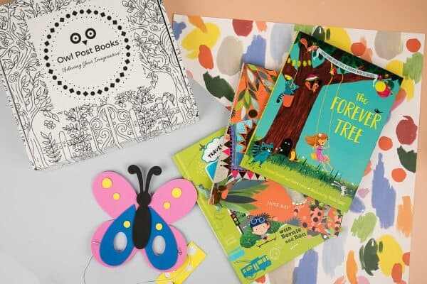 A birds eye photograph of an Owl Post Books box showing the box and contents of the box, which includes 3 childrens books for preschoolers and a craft or toy accessory