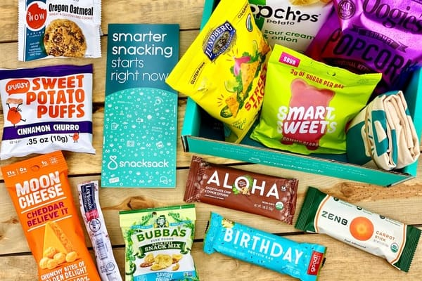 A birds eye photograph  of the SnackSack subscription box contents showing various healthy snacks against a wooden background
