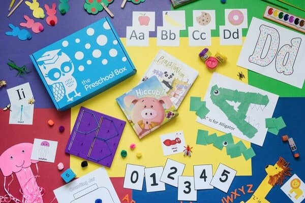 A birdseye photo showing the contents of The Preschool Box preschool in a box subscription box. Preschool phonics activites, number activities, books, and crafts are pictured