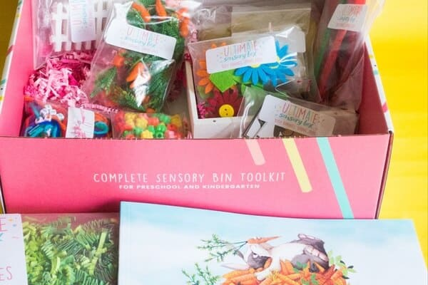 A photograph of the Ultimate Sensory Box preschool subscription box. The box is open and various sensory box contents are included inside in baggies.