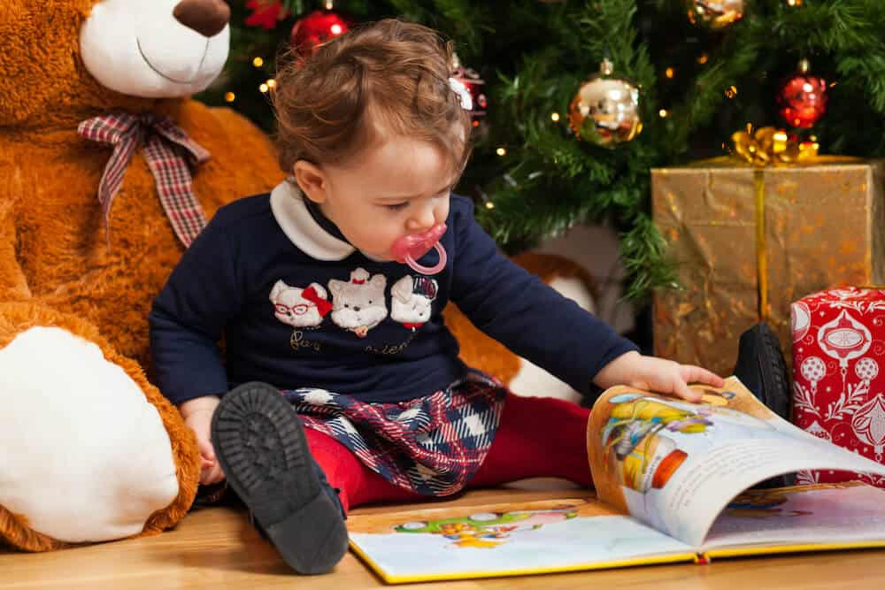 A toddler sitting in front of a Christmas tree and reading a Christmas book by himself
